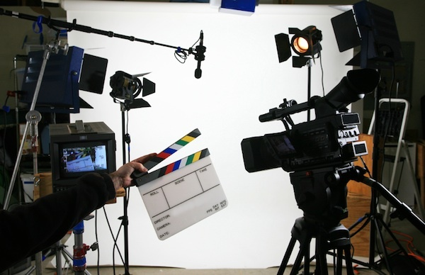someone holding a clapperboard in front of  a video camera, with a microphone and light
