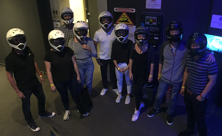 group shot of the direct response media team at the go kart track with their helmets on