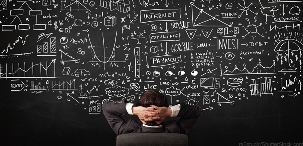 a man with his hands clasped behind his head looking at a chalkboard with sales statistics written on it