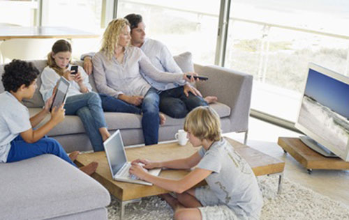 a family sitting in their living room with the parents watching TV,  one son on his laptop, one son on his Ipad and the daughter on her mobile phone