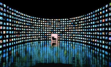 a man sitting on a chair surrounded by tv screens