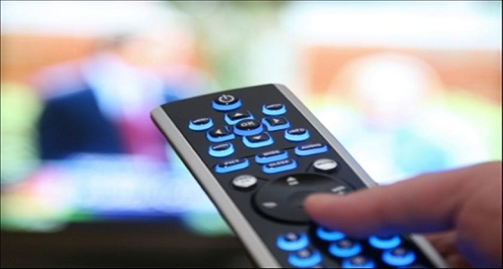 a finger pressing a button on the tv remote and pointing it at the tv screen